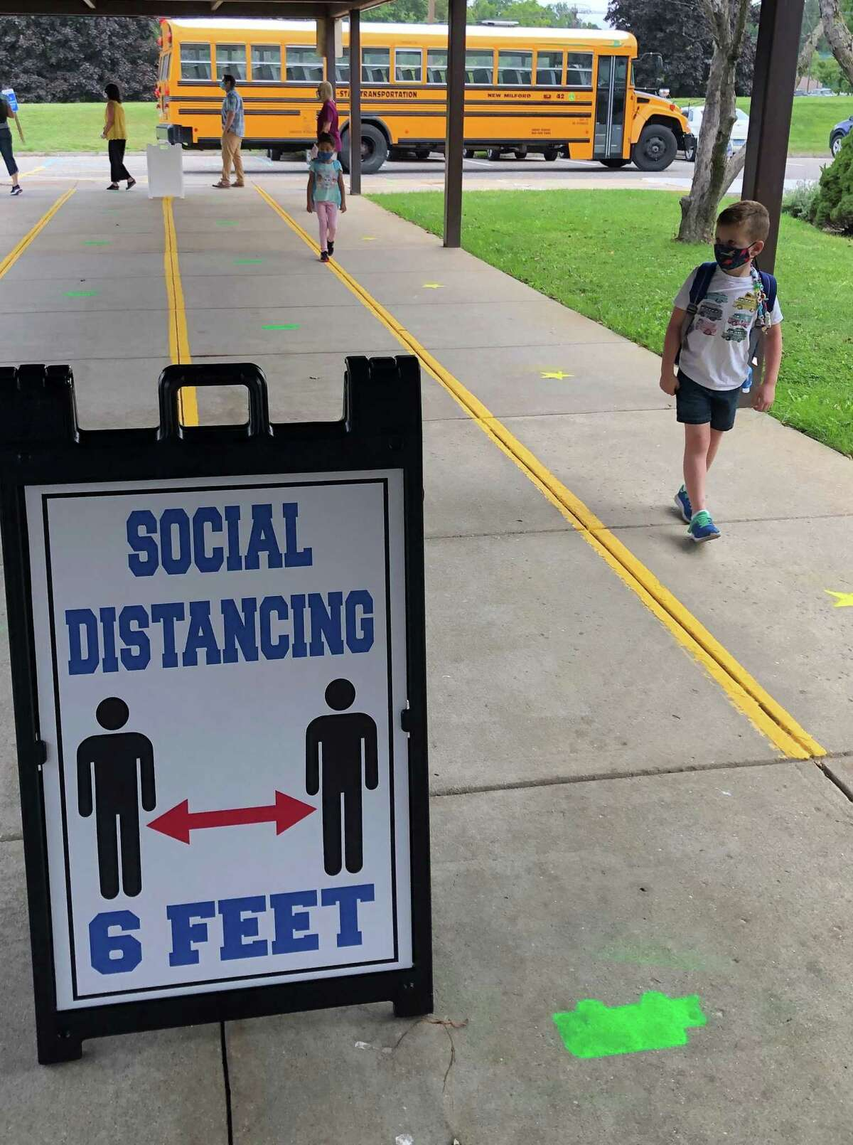Above, John MacDonald, a second grader, follows the marked sidewalk for his first day at Northville Elementary School on Sept. 8, 2020. The school year will start on time this Wednesday.