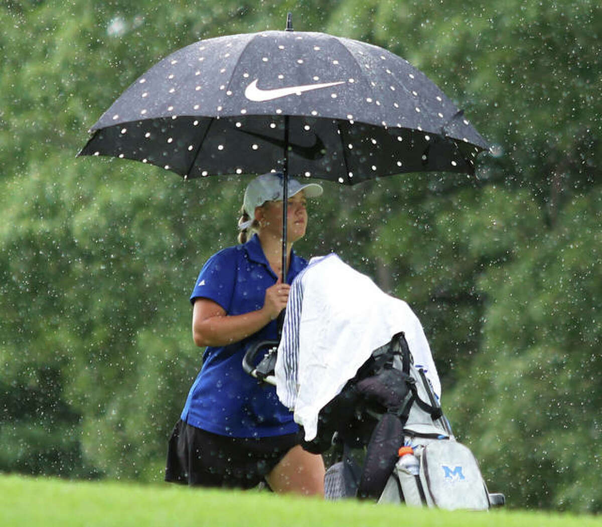 Marquette Catholic senior Audrey Cain walks up the fairway on hole No. 10 as rain falls after the second shot of her round Saturday at the Marquette Blast Off Tournament at Spencer T. Olin golf course in Alton.