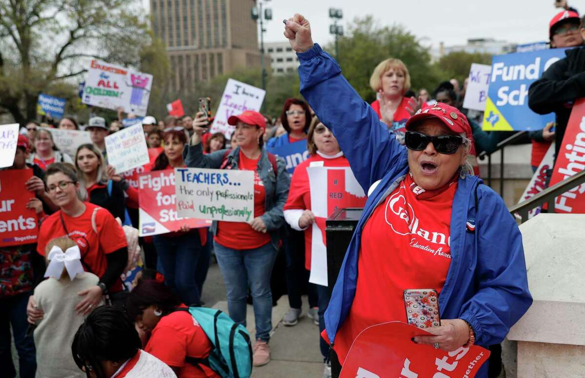In this March 11, 2019, photo, Koni Kaiwi, right, of Garland, Texas, joins other educators during a rally to support funding for public schools in Texas at the state Capitol, in Austin, Texas. Cost-cutting states are trying to keep schools happy as teacher unrest over low pay and overcrowded classrooms continues. But pressure from voters is forcing states to put more money on the table as much as much as picket lines. (AP Photo/Eric Gay)