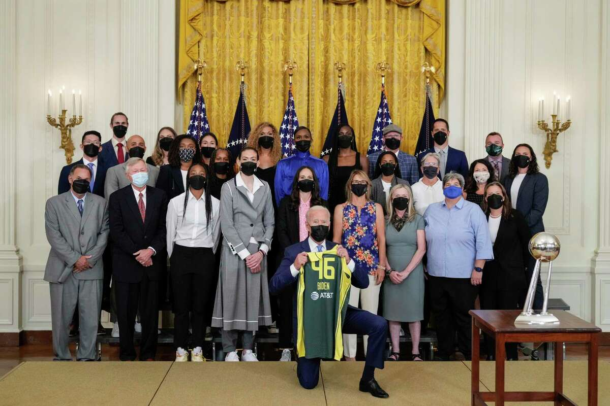 WASHINGTON, DC - AUGUST 23: U.S. President Joe Biden holds a jersey as he poses for a photo with the 2020 WNBA champions Seattle Storm in the East Room of the White House on August 23, 2021 in Washington, DC. The Storm defeated the Last Vegas Aces in the 2020 WNBA Finals to win their 4th title as a franchise. (Photo by Drew Angerer/Getty Images)