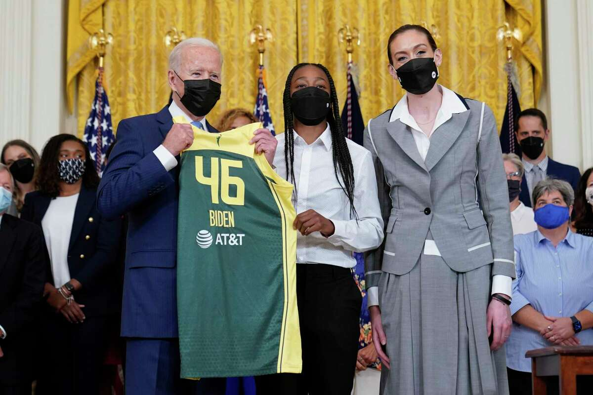 President Joe Biden, left, poses for a photo with Seattle Storm's Jewell Loyd, center, and Breanna Stewart, right, during an event in the East Room of the White House in Washington, Monday, Aug. 23, 2021, to celebrate their 2020 WNBC Championship. (AP Photo/Susan Walsh)