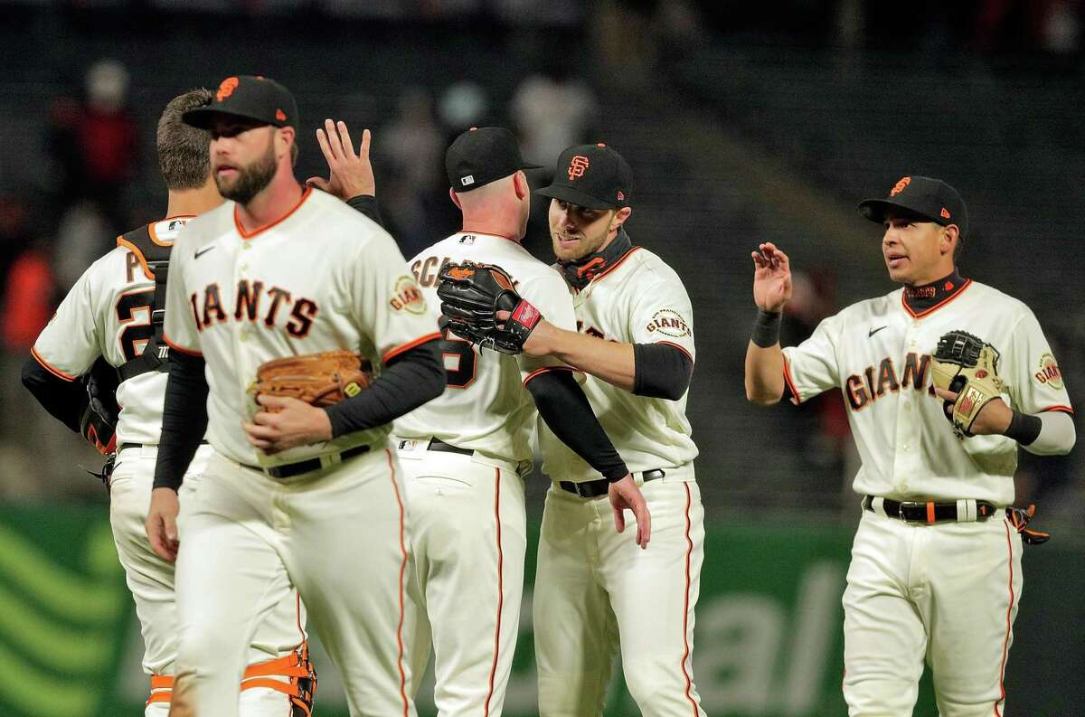 Austin Slater (13) hugs Anthony DeSclafani (26) after he pitched a complete game shutout and the San Francisco Giants defeted the Colorado Rockies 12-0 at Oracle Park in San Francisco Calif., on Monday, April 26, 2021.
