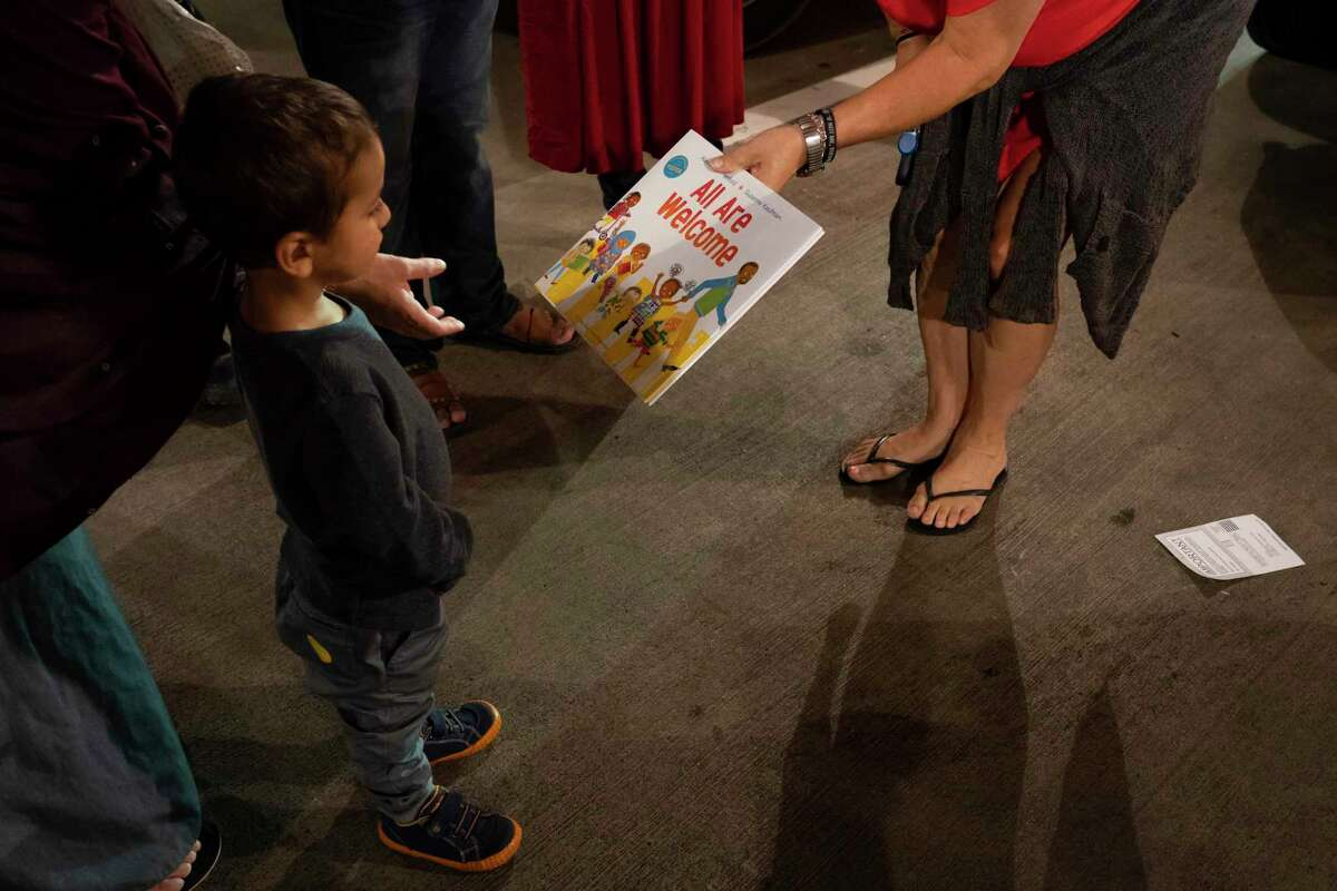 A book is given to the youngest member of a newly arrived Afghan family, Sunday, Aug. 22, 2021, at George Bush Intercontinental Airport in Houston.