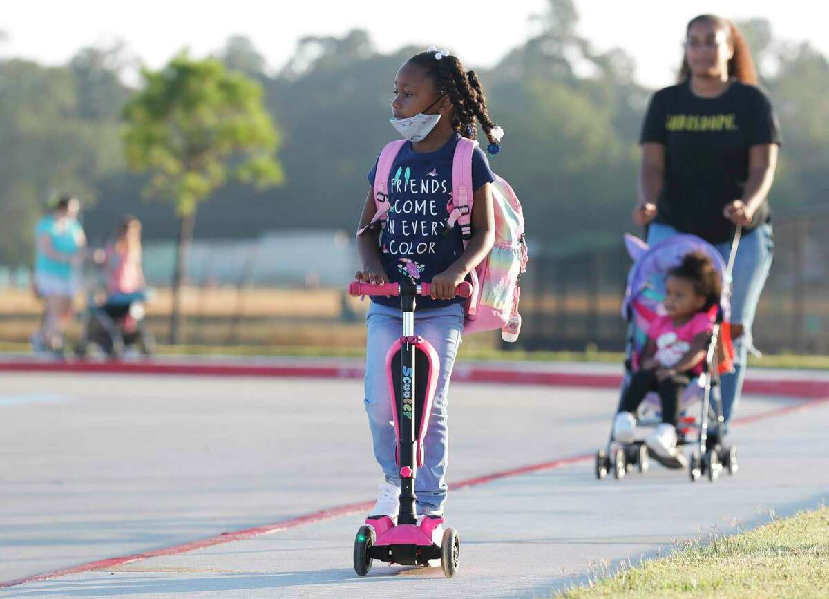 Alaysia Stephens rides her scooter in front of her mother Brittany on the first day of school at Conroe ISD's new Hope Elementary on Aug. 11. CISD reported 401 new student COVID-19 cases on Monday, which set a record for increases in daily cases for students in the district.
