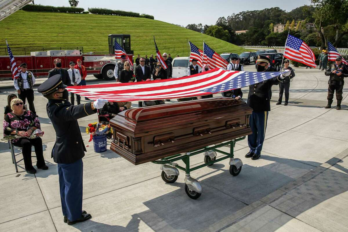 """Members of the Honor Guard prepare to fold the flag during a funeral honoring the life of Oakland native and World War II pilot Lt. Earl """"Buddy"""" Smith at Golden Gate National Cemetery in San Bruno, Calif."""