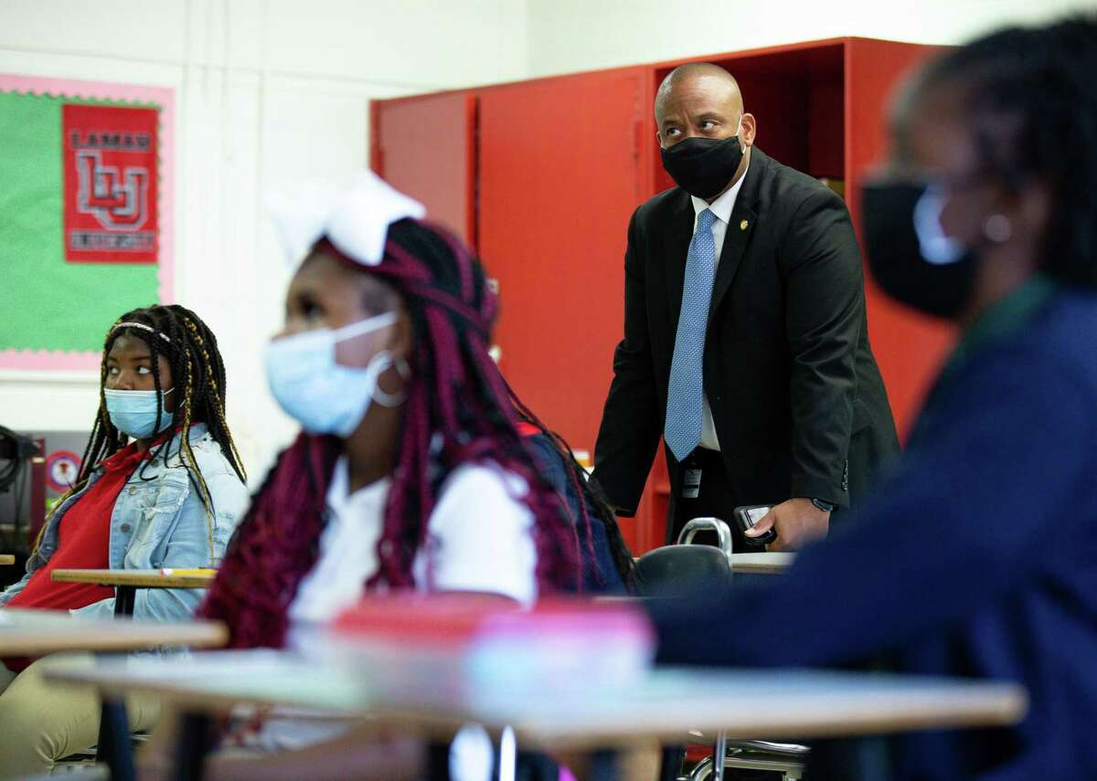 HISD superintendent Millard House II, center, visits a classroom at Attucks Middle School during the first day of school on Monday, Aug. 23, 2021, in Houston.