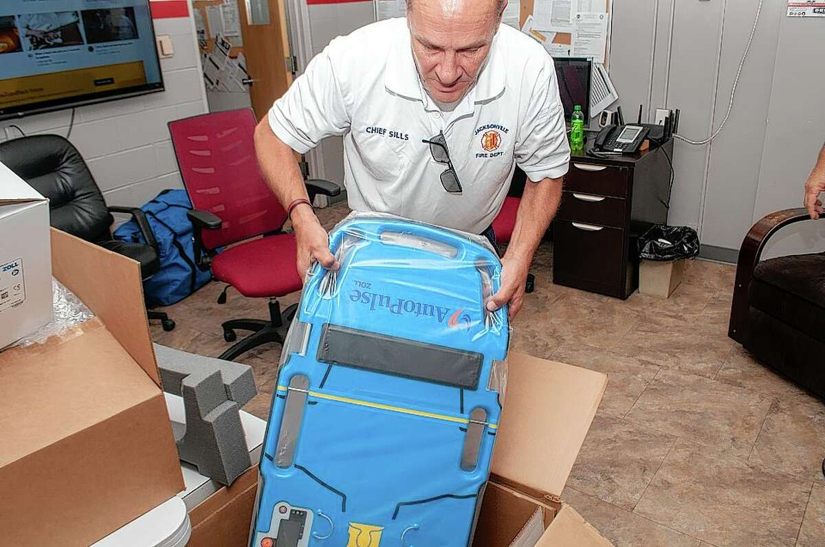 Jacksonville Fire Department Chief Doug Sills opens a box containing new automatic CPR equipment that will be available for EMTs.