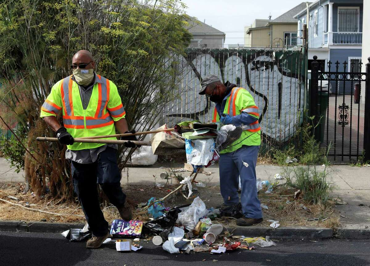 Marcus Leggett (left), a street maintenance leader, and Ayinde Osayaba, a street maintenance worker, pick up trash in Oakland. They are part of a team that drives through areas of Oakland that are known hot spots for illegal dumping.