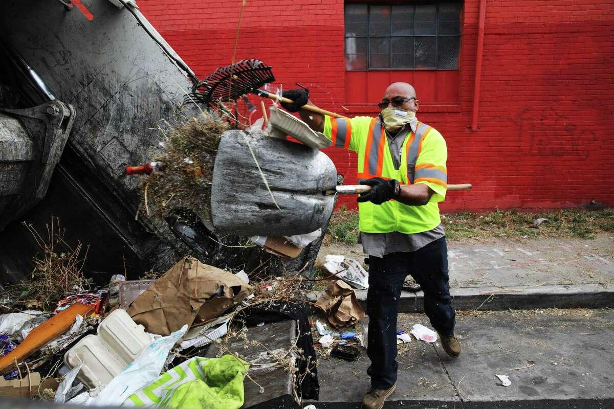 Marcus Leggett, a street maintenance leader for the Oakland Public Works Department, picks up trash in Oakland.