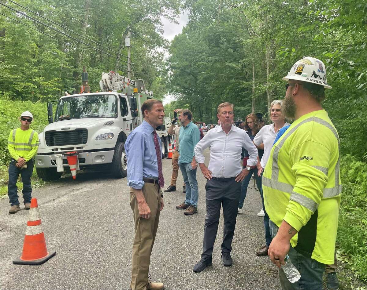 Sen. Richard Blumenthal, Gov. Ned Lamont and Canterbury First Selectman Chris Lippke speak with a utility worker, who came from New Hampshire to help respond to Tropical Storm Henri, as a crew works on a power line on Brooklyn Road in Canterbury on Monday.