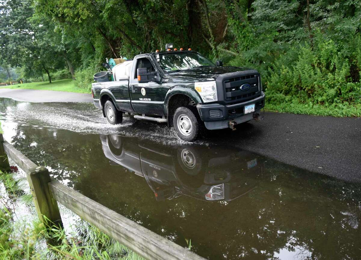 A Parks & Recreation truck drives through a puddle while cleaning up from Tropical Storm Henri at Greenwich Point Park in Old Greenwich, Conn. Monday, Aug. 23, 2021. Henri doused the area with rain but left minimal damage as the hurricane was downgraded to a tropical storm before making landfall.