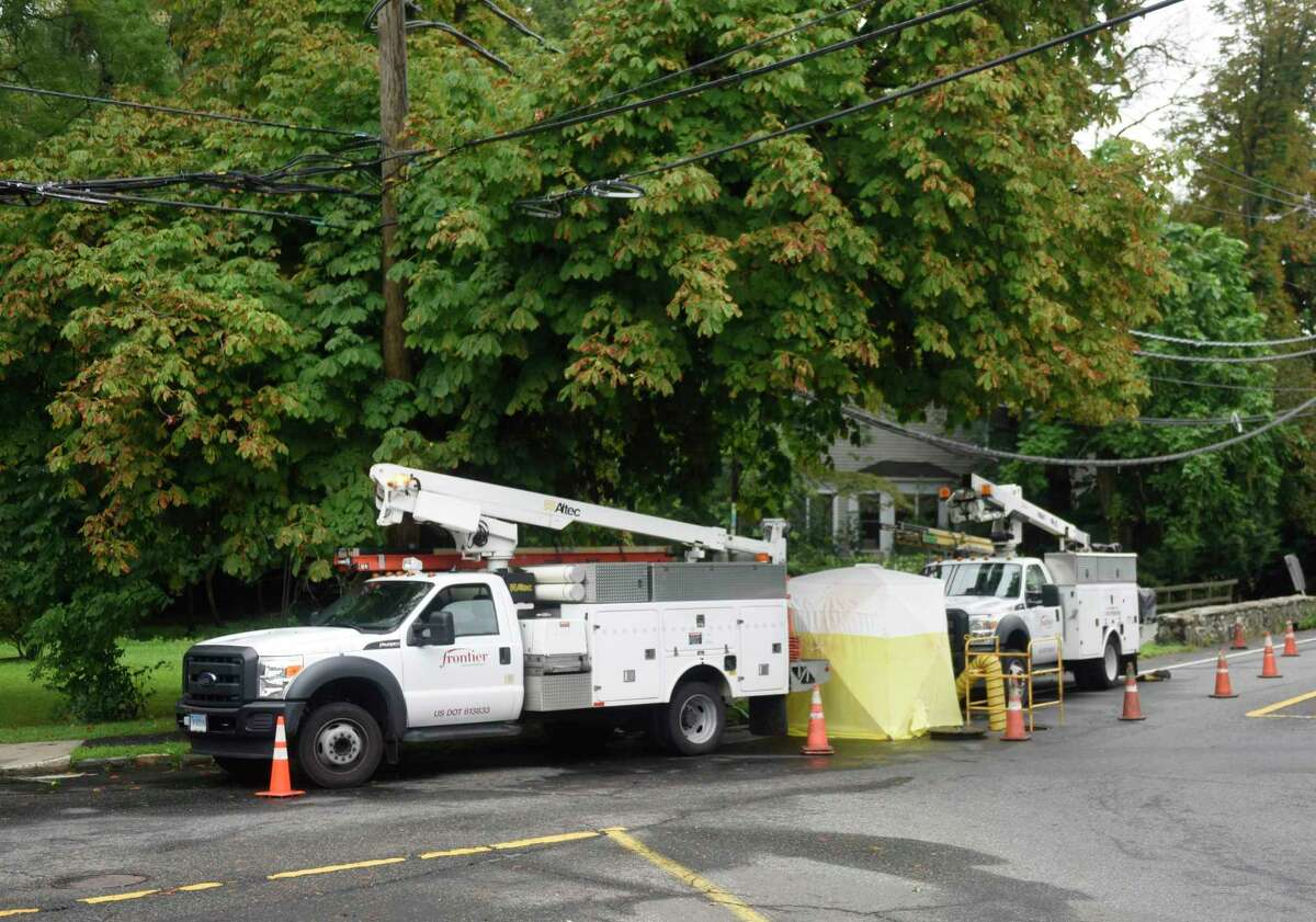 Frontier Communications trucks repair a damaged line the day after Tropical Storm Henri hit Old Greenwich, Conn. Monday, Aug. 23, 2021. Henri doused the area with rain but left minimal damage as the hurricane was downgraded to a tropical storm before making landfall.