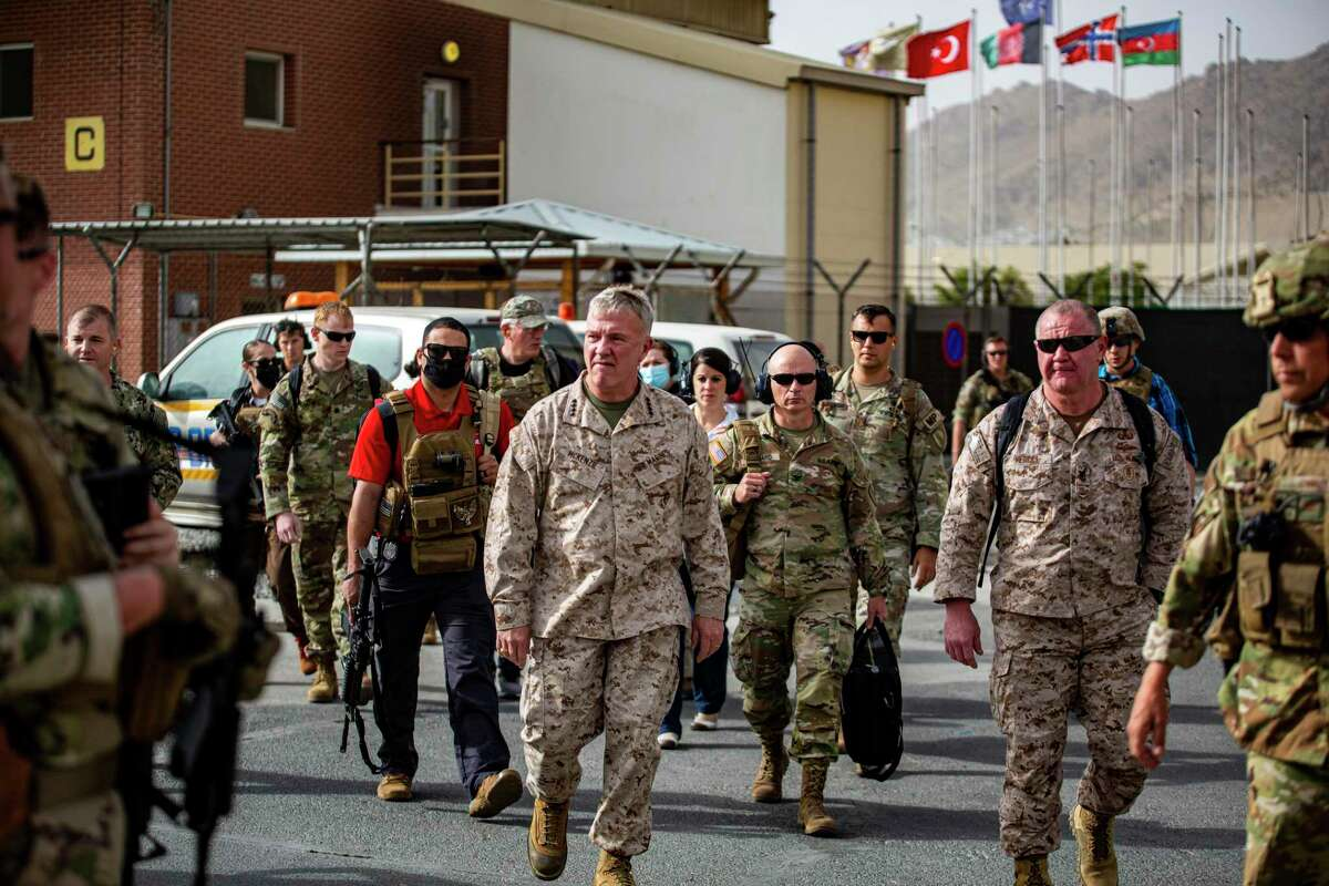 Commanding Gen. U.S. Central Command Kenneth F. McKenzie, center, tours an evacuation control center at Hamid Karzai International Airport, Afghanistan, Tuesday, Aug. 17, 2021.