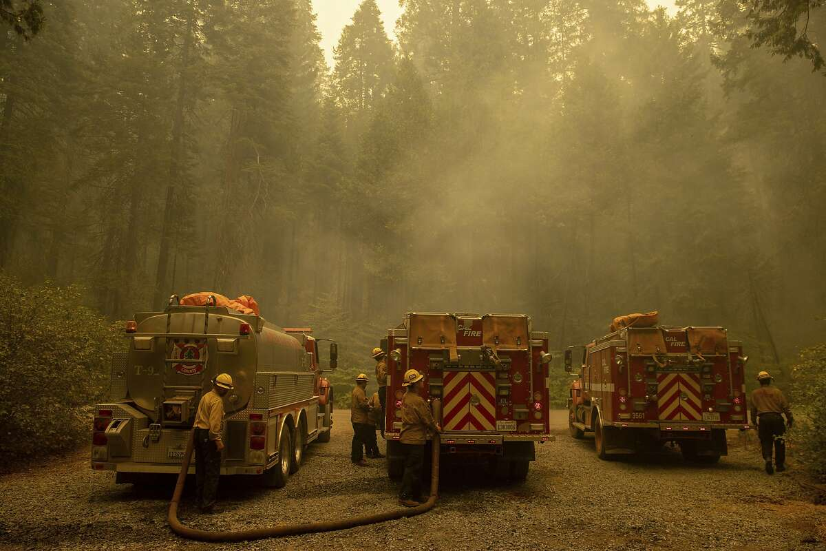 Firefighters refill water while fighting the Caldor Fire on Hazel Valley Road east of Riverton, Calif. on Aug. 19, 2021.