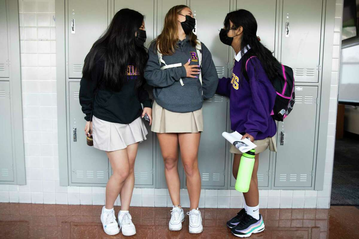 A group of girls socialize in the halls before class during the first day of coed in-person learning at Archbishop Riordan High School in San Francisco on Thursday.