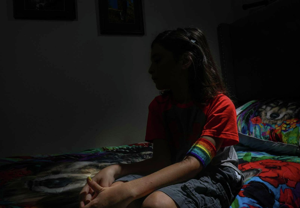 """Tristan, a nonbinary fifth-grade student, poses for a portrait in their bedroom Monday, Aug. 23, 2021, in Magnolia. The child's mother said the child has been in in-school suspension because of a Magnolia ISD policy mandating short hair. """"The school is digging in its heels, and they don't see how it's affecting [them] and our family,"""" the mother said."""
