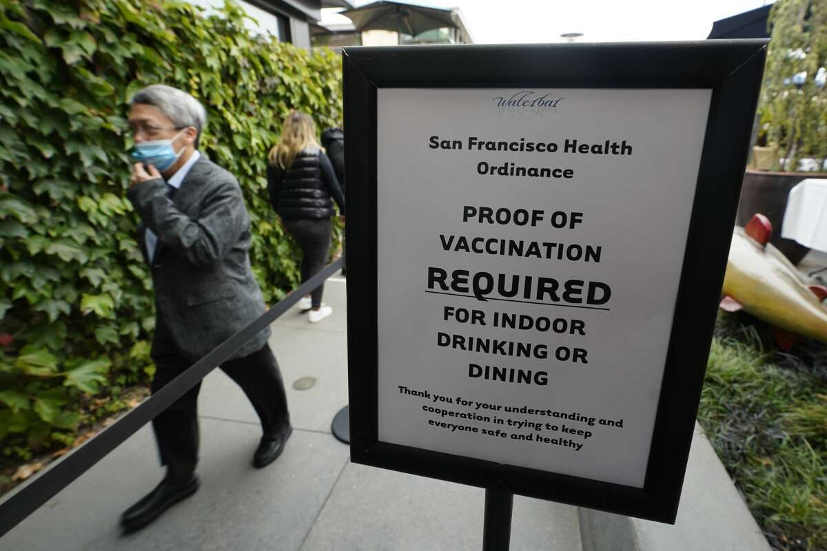 A diner makes his way into the Waterbar restaurant past a proof of vaccination sign Friday, Aug. 20, 2021, in San Francisco.