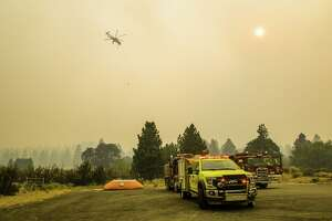 A helicopter prepares to drop water on the Dixie fire in Aug. 20, 2021.