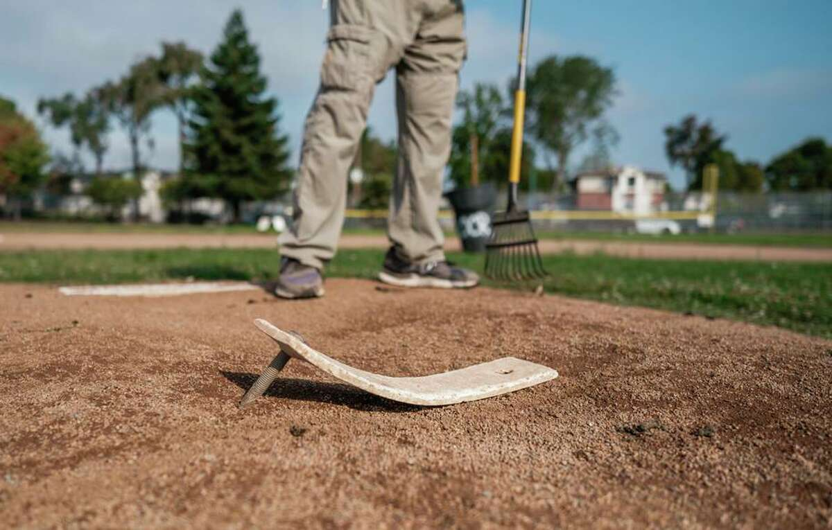 A worker tends to the mound before the start of a Babe Ruth League 10-and-under baseball game in Oakland.