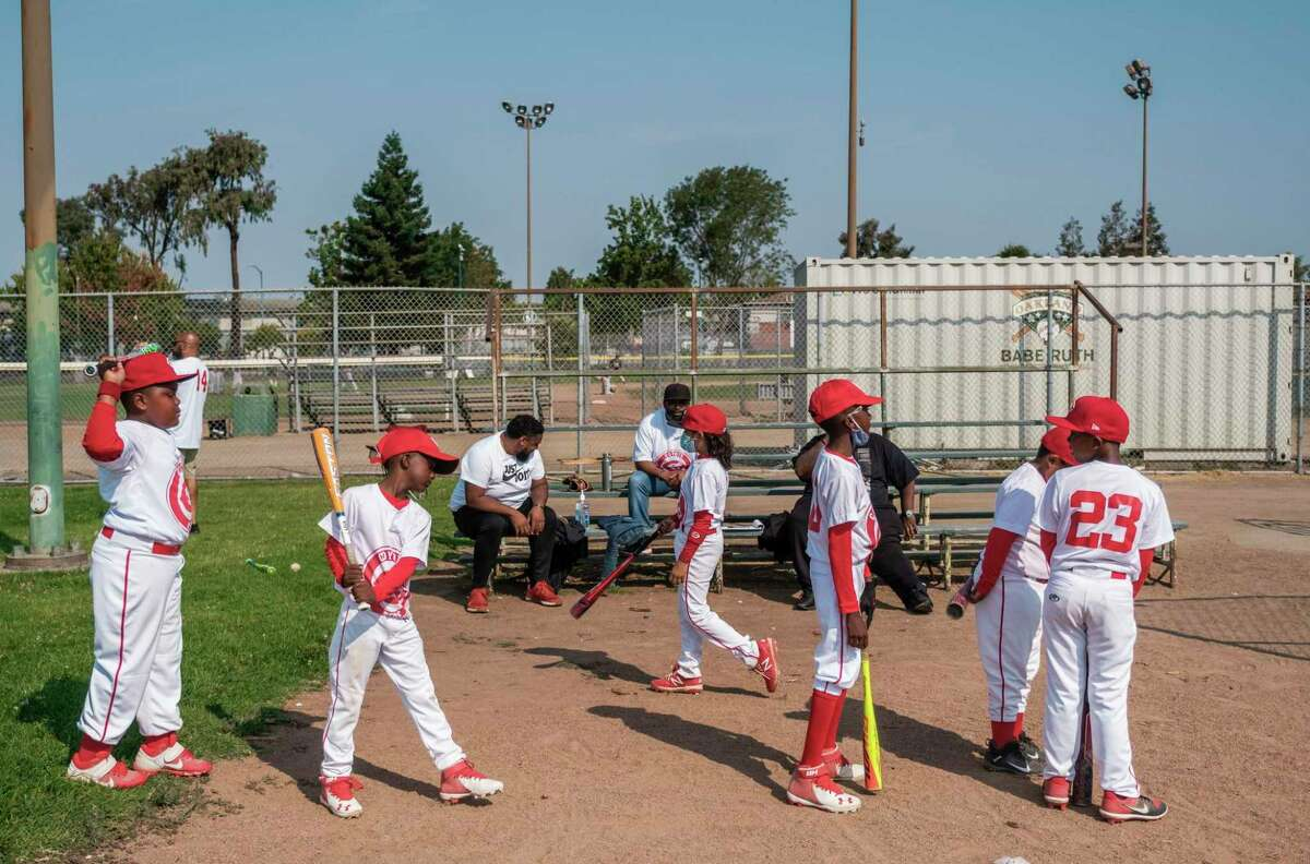 Players warm up before a 10-and-under baseball game. Currently fewer than 250 children participate in the Oakland Babe Ruth League.