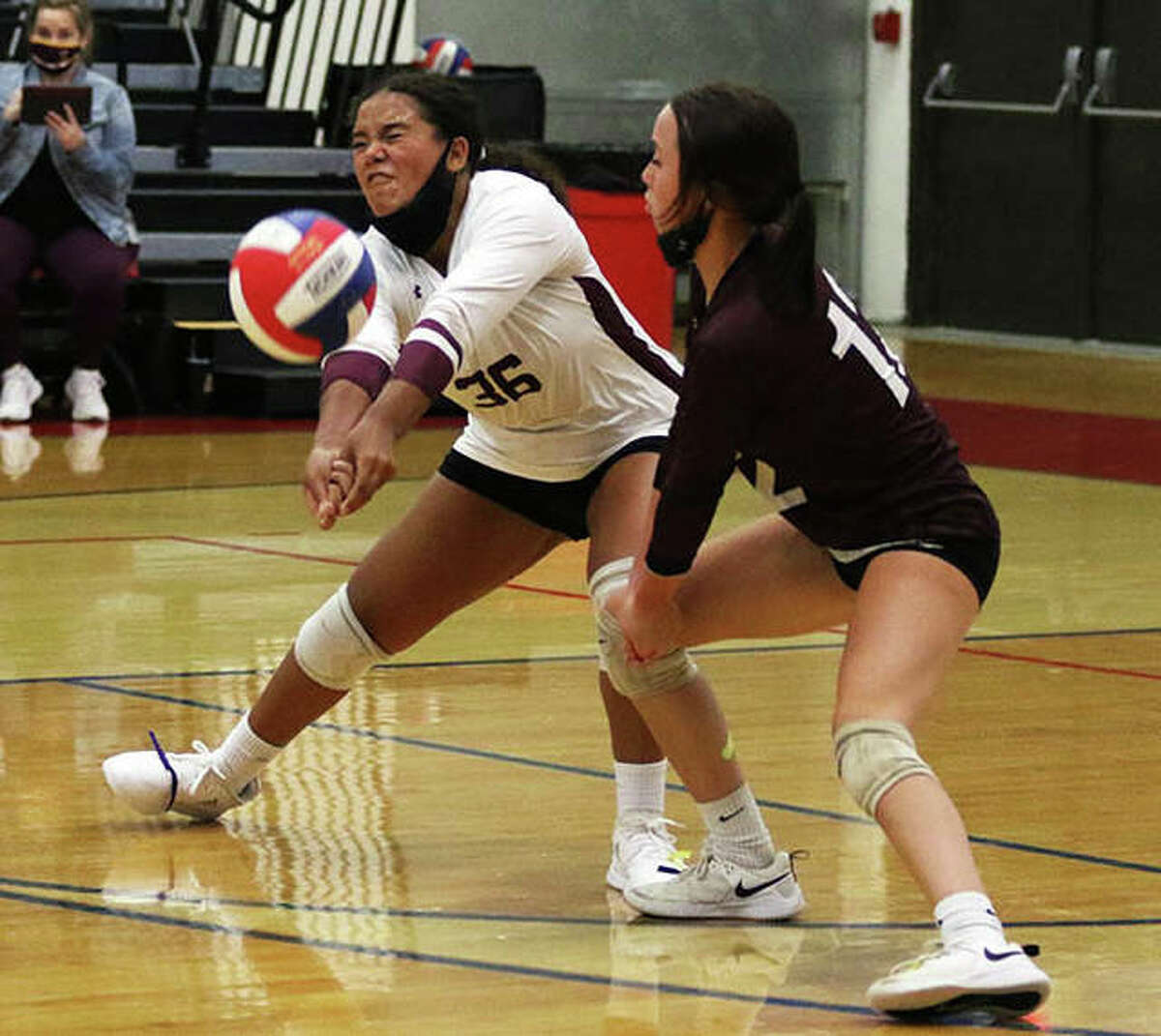 EA-WR's Reaghan William (left) receives a serve in front of Oilers libero Zenn Wilson in a match against Marquette on Monday night at the Roxana Tourney.