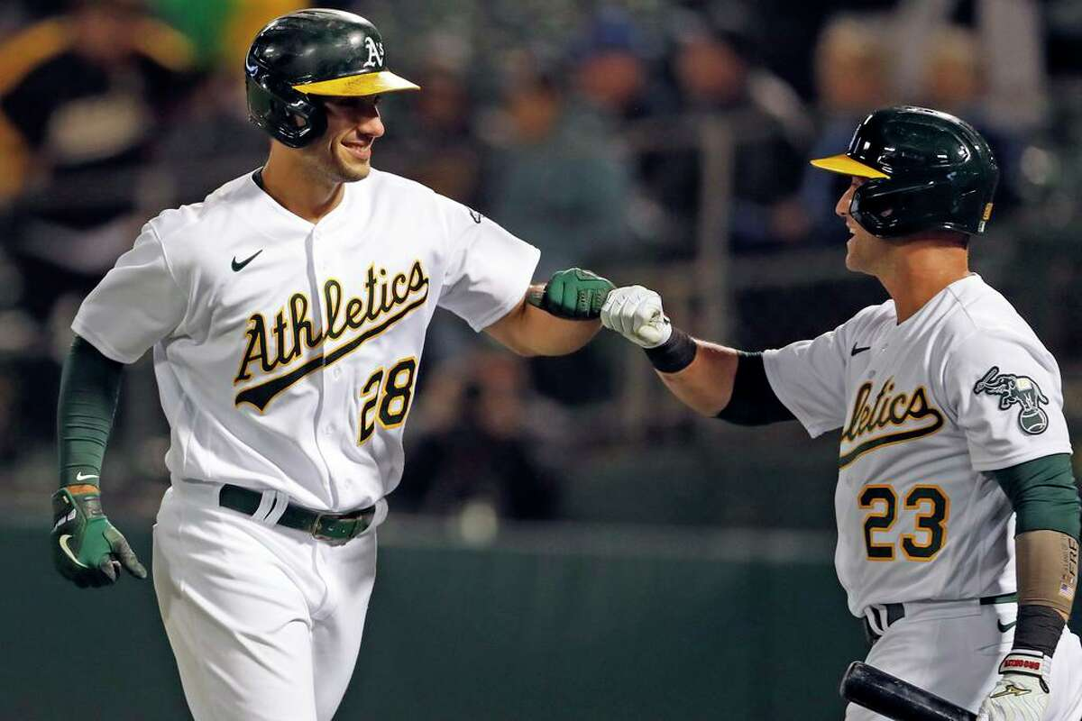 Oakland Athletics' Matt Olson fist bumps Yan Gomes after hitting go-ahead solo home run in 6th inning against Seattle Mariners during MLB game at Oakland Coliseum in Oakland, Calif., on Monday, August 23, 2021.