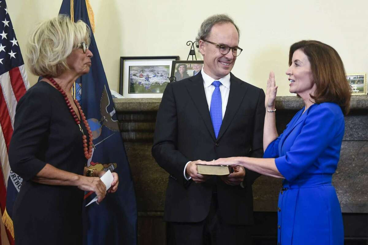 New York Chief Judge Janet DiFiore, left, swears in Kathy Hochul, right, as the first woman to be New York's governor while her husband Bill Hochul holds a bible during a swearing-in ceremony in the Red Room at the state Capitol, early Tuesday, Aug. 24, 2021, in Albany, N.Y.