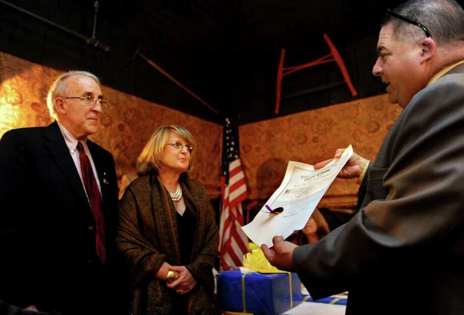 Walter Sherman III presents the official charter to Nancye and Bruce Fritz during the celebration of the creation of the Westport charter of the Lions Club at The Red Barn in Westport on Wednesday, September 15, 2010. Photo: Lindsay Niegelberg / Connecticut Post