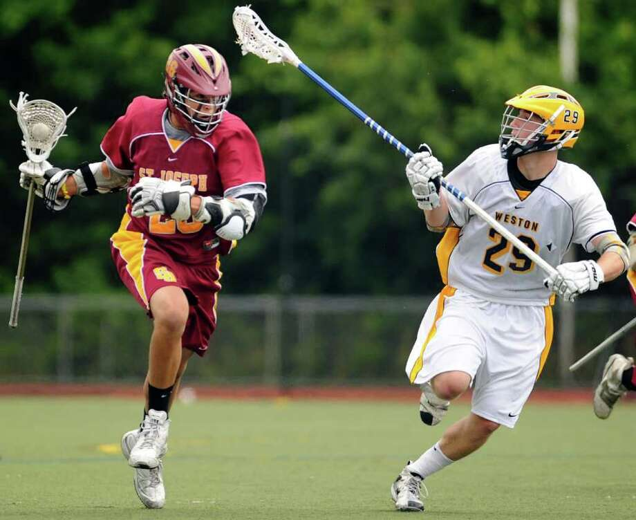 St. Joseph's Mark Snellman drives the ball down the field as Weston's William Miller defends during the Lacrosse Class S State Finals Saturday June 12, 2010 at Brien McMahon High School in Norwalk. Photo: Autumn Driscoll / Connecticut Post