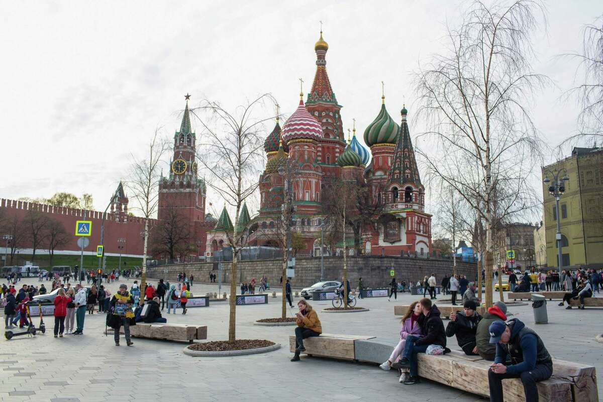 Visitors walk by the Spasskaya tower of the Kremlin and Saint Basil's Cathedral in Moscow on May 2, 2021.