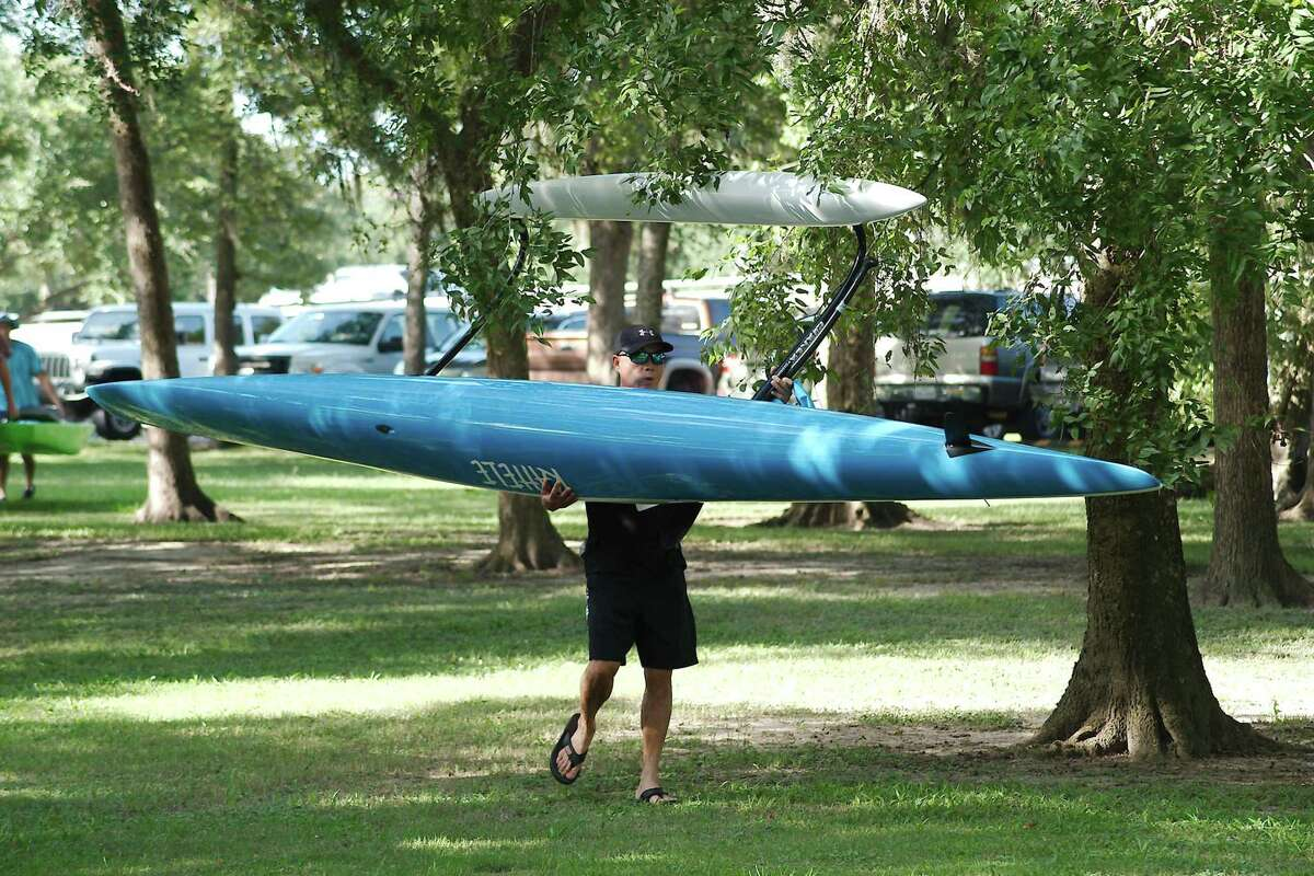 Michael Zheng carries his kayak as he prepares to launch on Clear Creek for the Clear Creek Paddle Race.