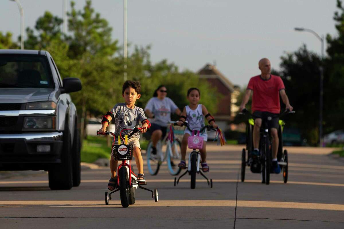 Four-year-old Ezra Burke leads the way on a family bike ride through his neighborhood Wednesday, Aug. 12, 2020, in Houston. The Burkes have been finding ways to keep their young children active as the COVID pandemic has effected school and other extracurricular activities.