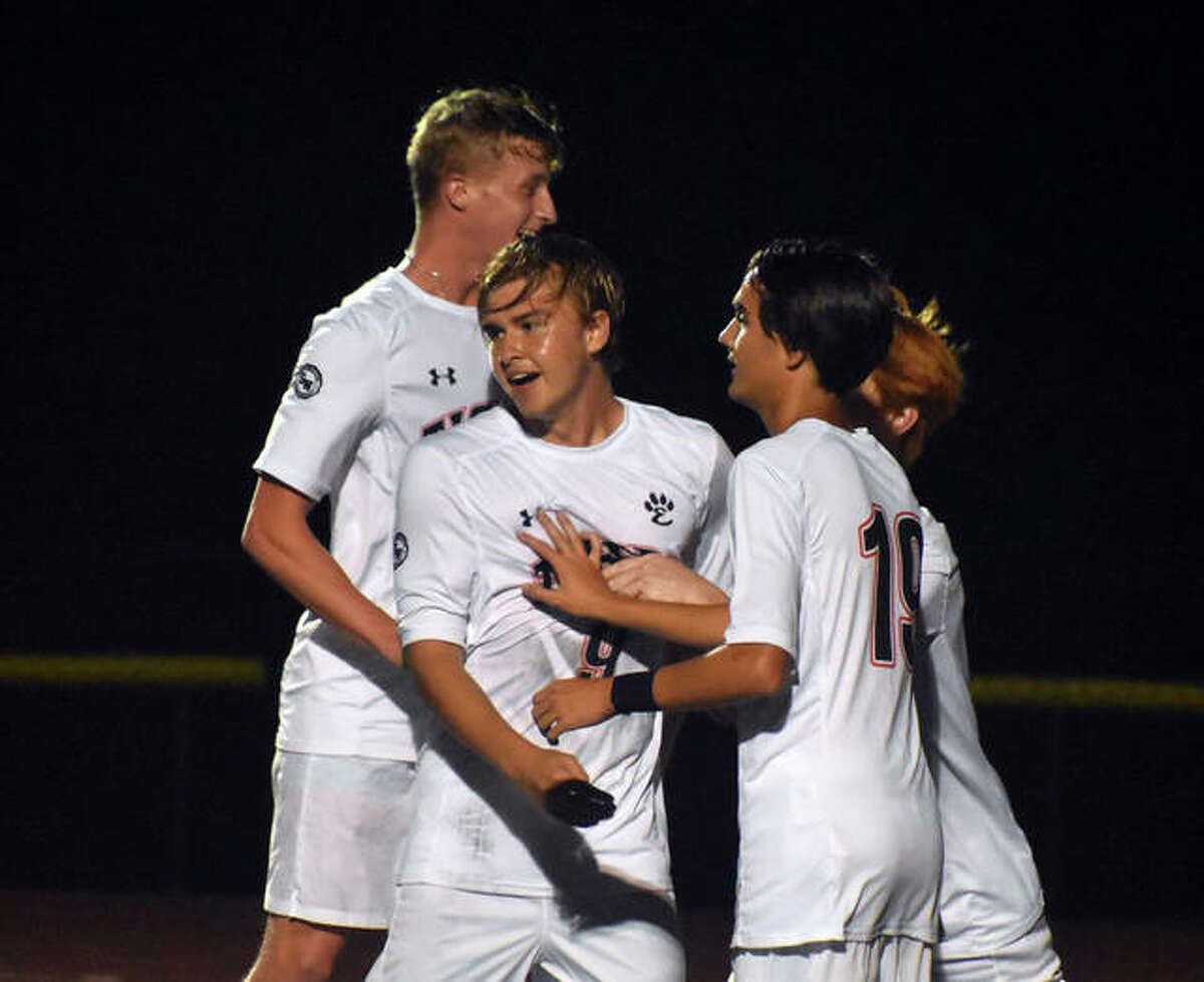 Edwardsville's Brendan James, center, is congratulated after scoring on a PK in the second half against Granite City.