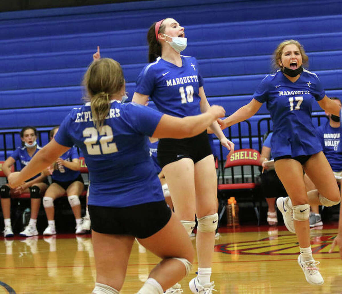 Marquette's Abby Williams (10) celebrates her ace on match point to beat EA-WR with Explorers teammates Torrie Fox and Shay O'Leary on Monday night in the Roxana Tourney at Milazzo Gym.