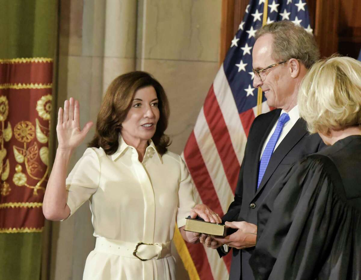 New York Chief Judge Janet DiFiore, right, swears in Kathy Hochul as the first woman to be governor of New York, while her husband Bill Hochul holds a bible during a ceremonial swearing-in ceremony at the Capitol, Tuesday, Aug. 24, 2021, in Albany, N.Y.
