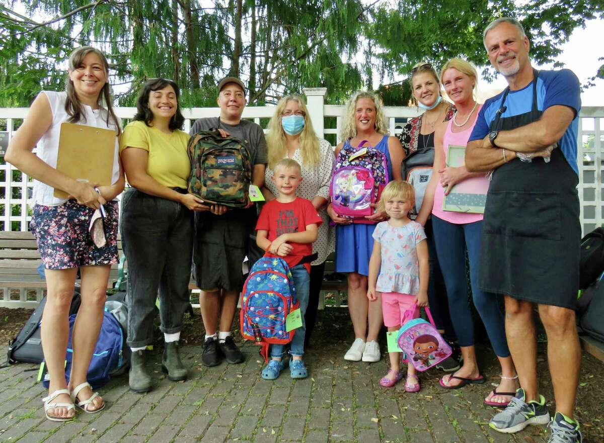 Jax Lee and Grace Burbridge, front and center, with new backpacks courtesy of a town-wide drive spearheaded by the CDR, including, from left, Laura Gunneson, Danielle Capalbo, Amos Parker, Diane Pappacoda, Andrea Savino, Courtney Rosenberg, and Stuart Sokol. Also pictured is Leah Burbridge, mother of Jax Lee and Grace, second from right.