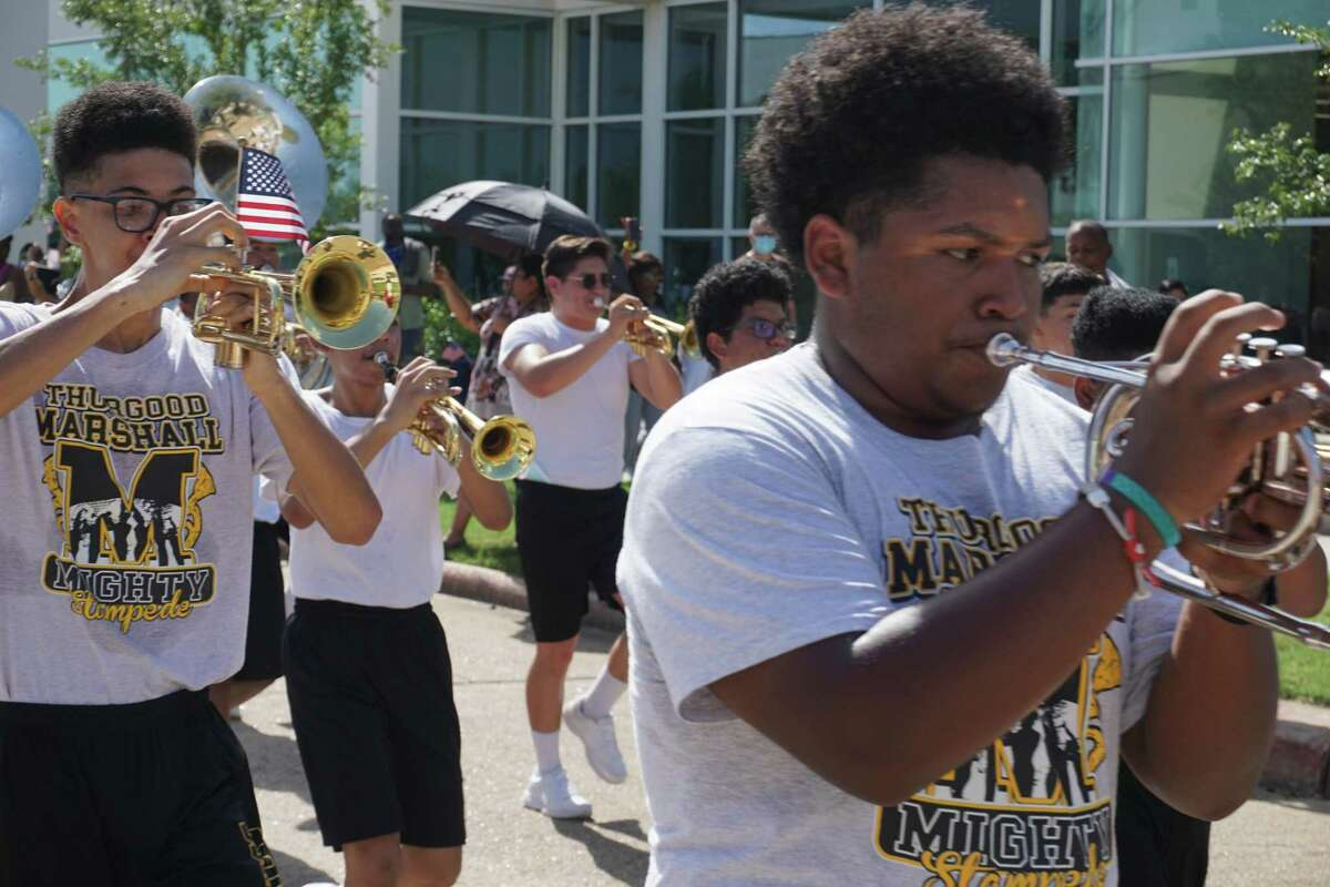 Members of the Thurgood Marshall High School band march during a celebration for Missouri City's hometown Olympic medalist on Saturday, Aug. 21, at Community Center Plaza.