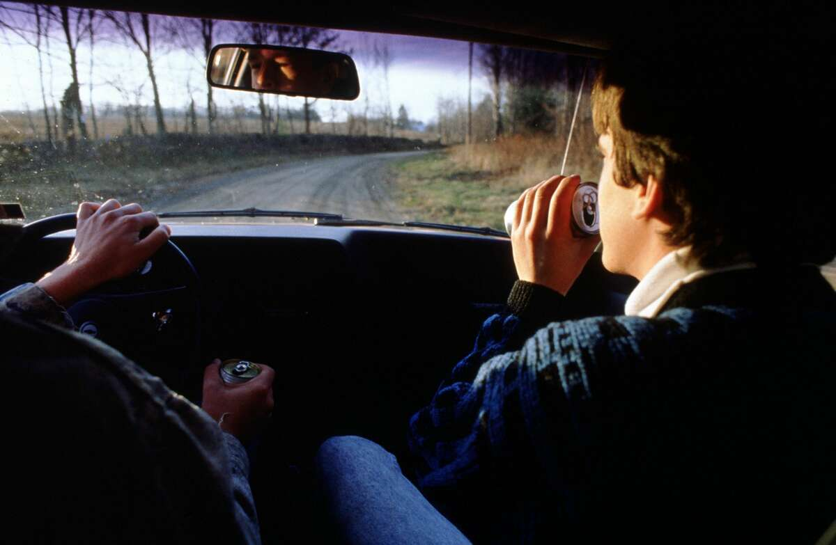Pictured is two teenagers drinking and driving.