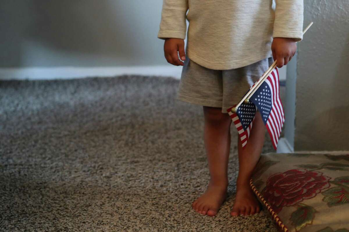 """The 3-year old son of """"Khan"""", an Afghan ally, holds a pair of American flags after fleeing the Taliban in Afghanistan on Monday, Aug. 23, 2021 in Houston. The family arrived in Houston Sunday night."""