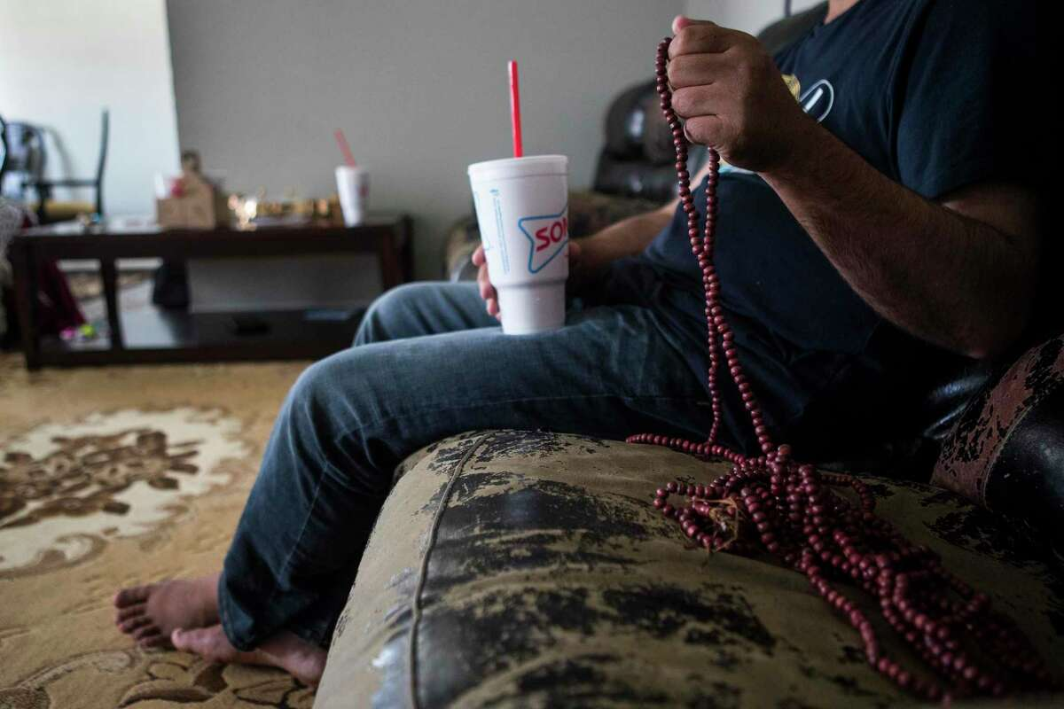 """""""Khan"""", an Afghan Special Immigrant Visa holder, sits with his family as he settles into an apartment they are staying in after fleeing the Taliban in Afghanistan on Monday, Aug. 23, 2021 in Houston. The family arrived in Houston Sunday night."""