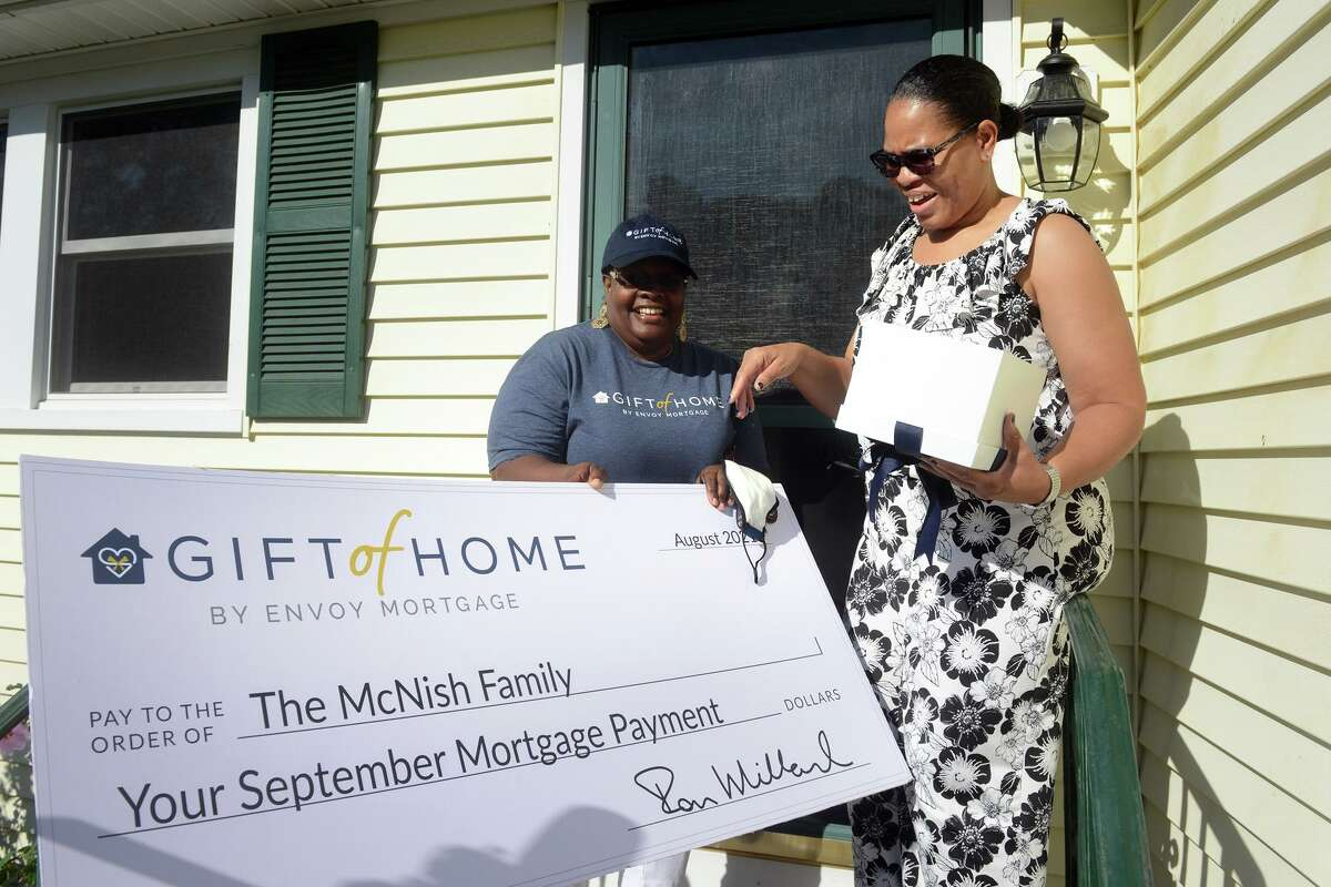Melissa Mason, left, branch manager for Envoy Mortgage, in Fairfield, presents a check to Irana McNish on the front steps of her home in Derby, Conn. Aug. 24, 2021. Envoy chose to award McNish by covering her monthly mortgage payment to honor her efforts working as a nursing assistant during the COVID-19 pandemic. McNish works at Edgehill Rehabilitation, in Stamford.