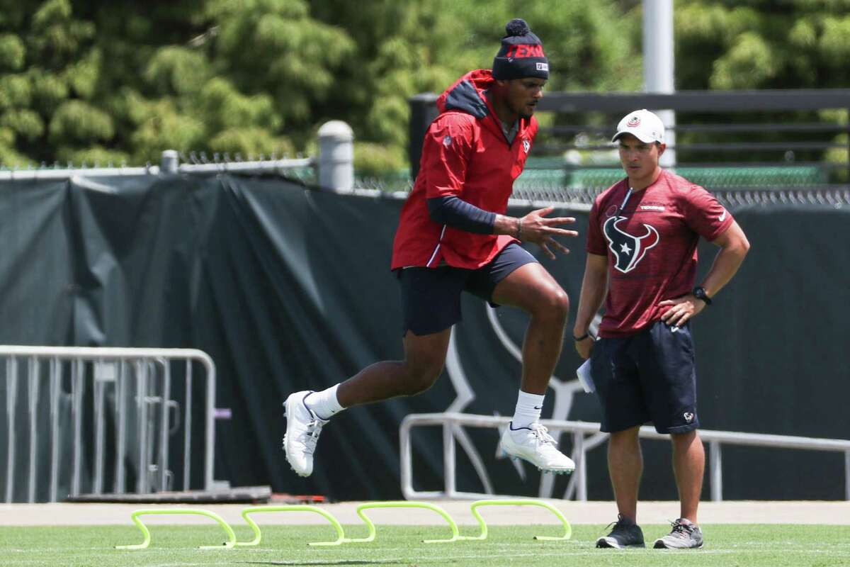 Texans quarterback Deshaun Watson works out on the side as a team staffer observes during Tuesday's practice.