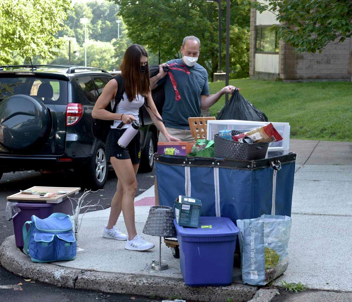Kalynna Hauser, of Orange, a junior nursing student, left, gets help from her father Greg Hauser moving into her Western Connecticut State University westside campus dorm. Tuesday, August 24, 2021, Danbury, Conn.