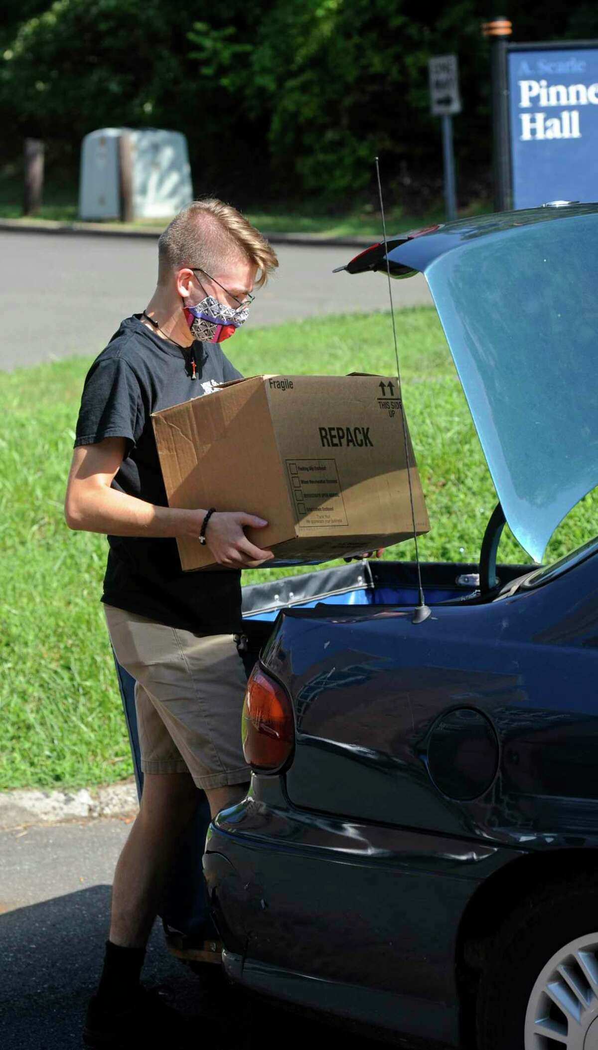 Adam Jackson, of Branford, a junior music education major, unpacks his car while moving into his Western Connecticut State University westside campus dorm. Tuesday, August 24, 2021, Danbury, Conn.