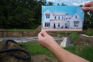 Vince Santilli holds up a print of the house he and his wife, Dianne Santilli, are building on Sunday, Aug. 22, 2021, in Stillwater, N.Y.