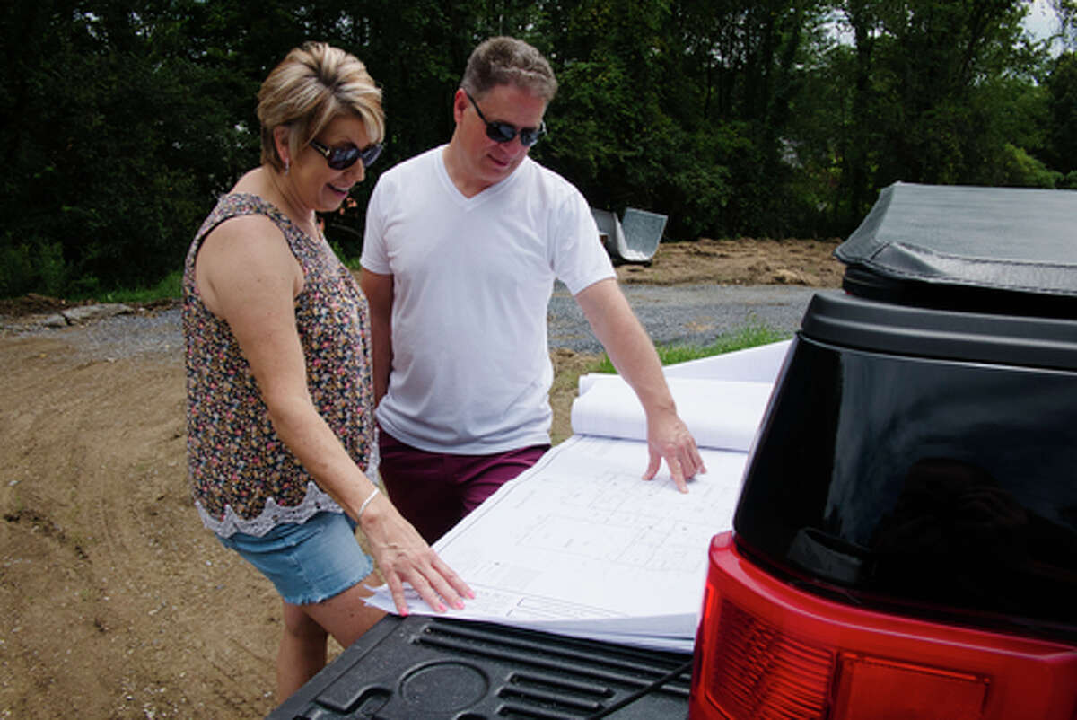 Dianne Santilli, left, and her husband Vince Santilli look over the architectural plans of the home they are building in Stillwater.
