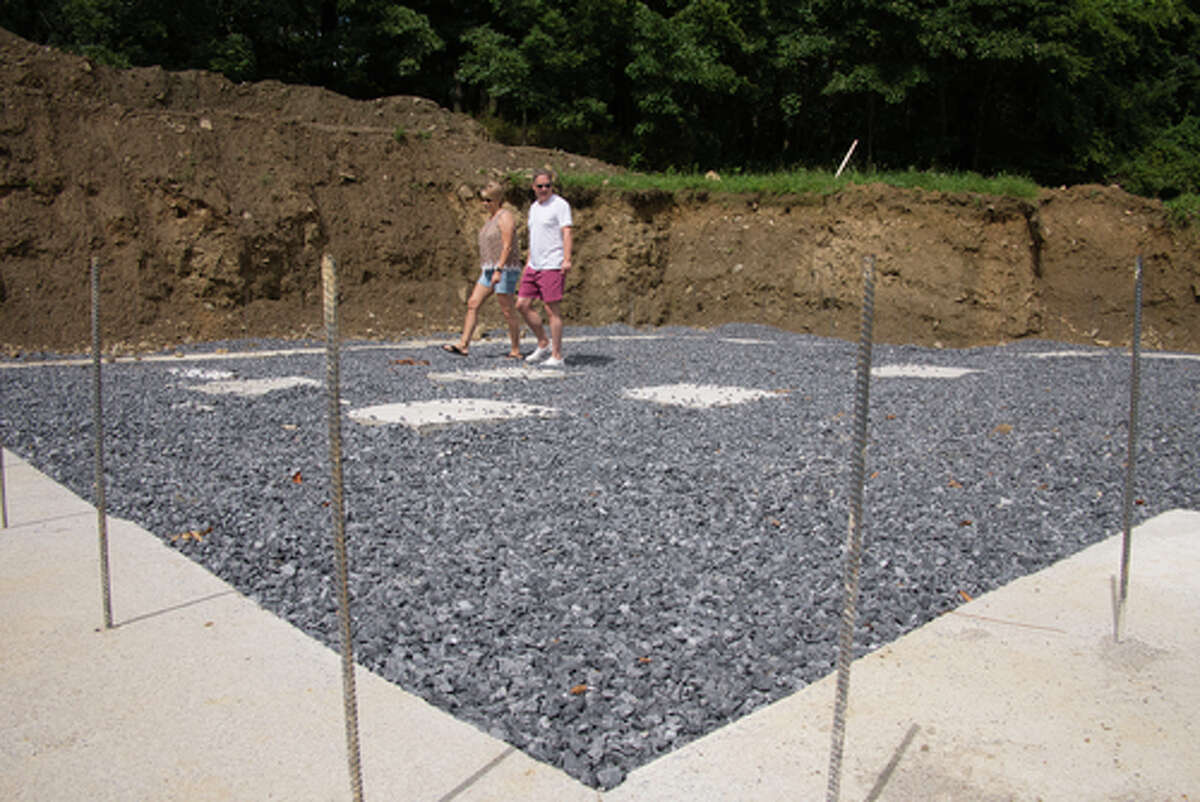 Dianne Santilli, left, and her husband Vince Santilli look over the footings of the home they are building in Stillwater before the installation of foundation wall forms.