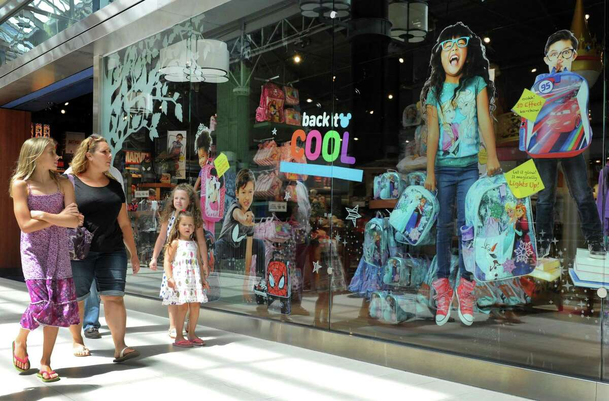 Shoppers stroll in August 2015 past The Disney Store at Danbury Fair in Danbury, Conn. The store is closing in September 2021 as Walt Disney shifts its retail emphasis to online sales.