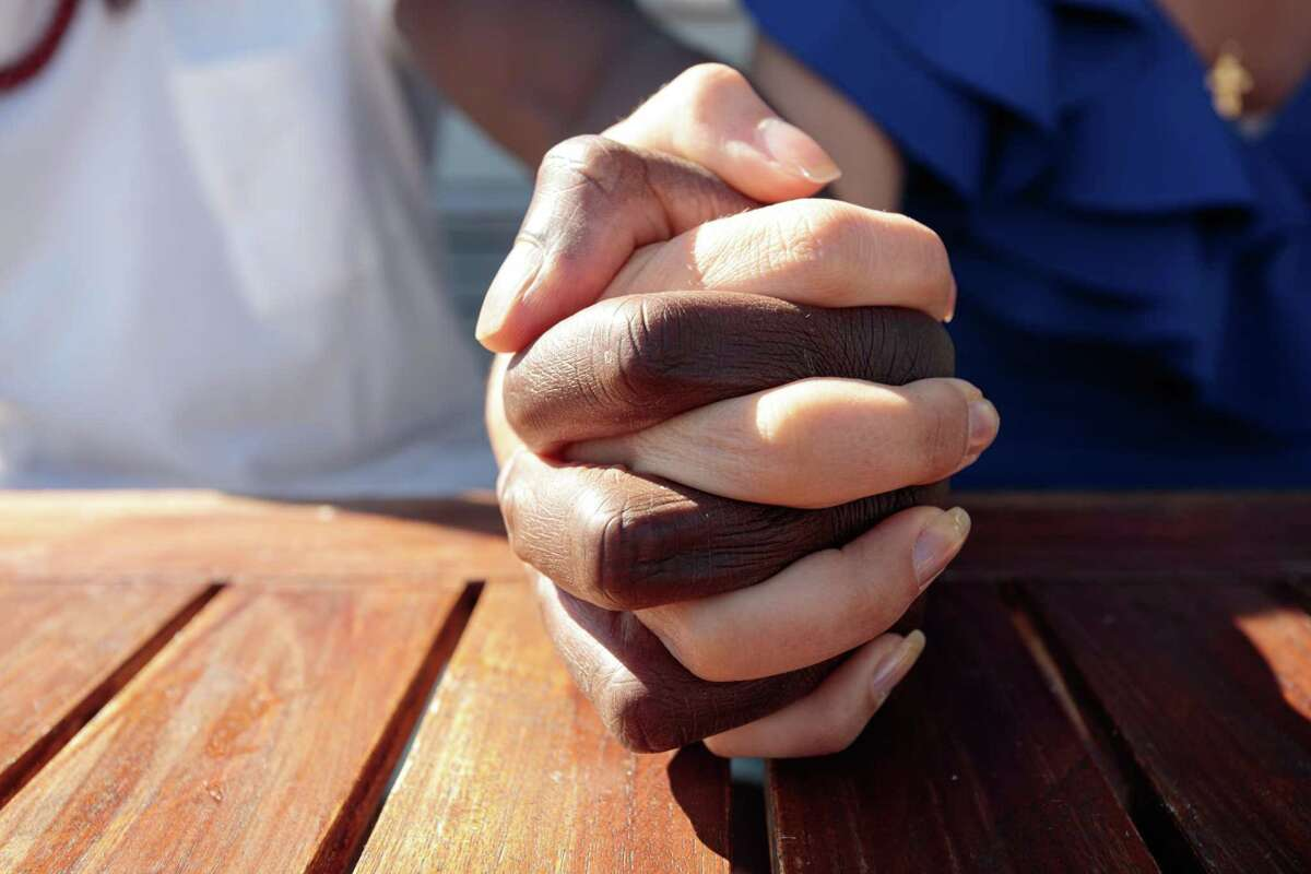 Hands joined together, close-up, different races.