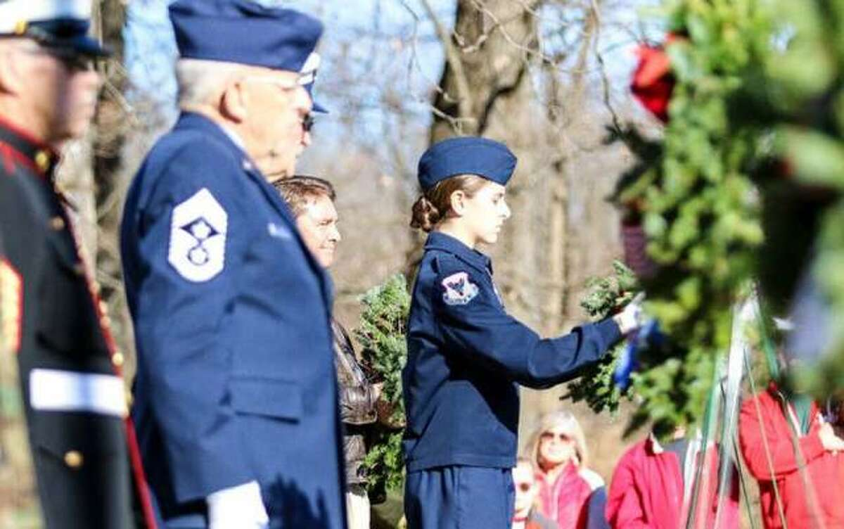 """In this 2017 photo, participants help place some of the 560 wreaths on graves at the Alton National Cemetery as part of """"Wreaths Across America."""""""